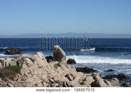 This is an image of the rocky shore line of Pacific Grove, California taken on a clear sunny day/