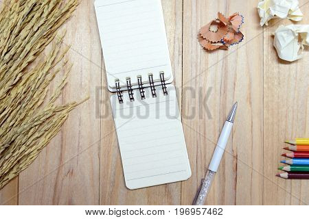 Small note book paper (notepad) for writing information with pen color pencil and crumpled paper balls on wooden table. view from above