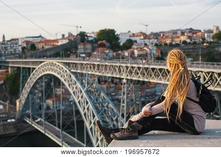 Young woman looks at Dom Luis I bridge across the Douro river in Porto, Portugal.