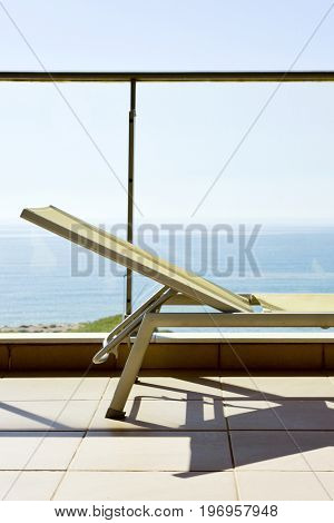 closeup of a sunlounger in a balcony, with the ocean in the background