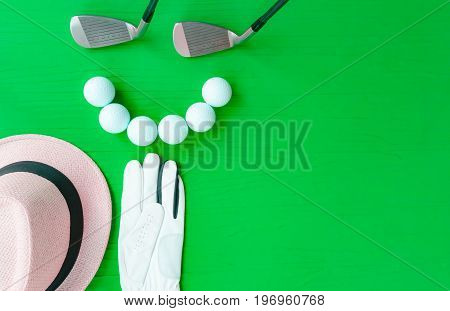 Golf concept : panama hat golve golf balls golf clubs on wooden table. Flat lay with copy space.