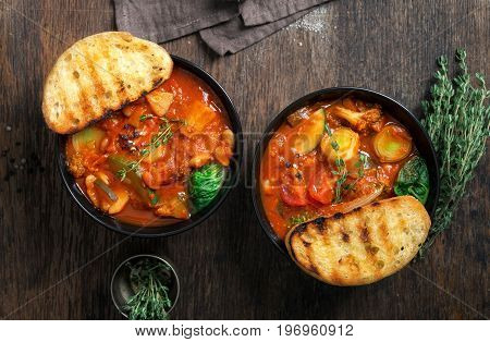 Two bowl of soup minestrone with seasonal vegetables on wooden table close up top view. Italian food