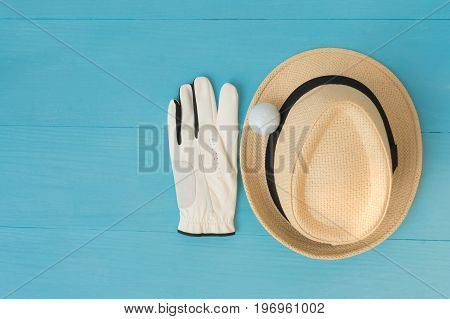 Golf concept : panama hat glove golf balls on wooden table. Flat lay with copy space.