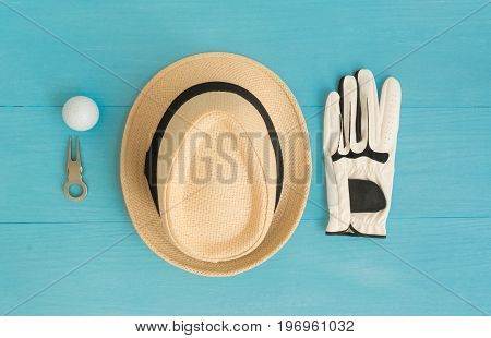 Golf concept : panama hat glove golf balls divot repair tool on wooden table. Flat lay with copy space.