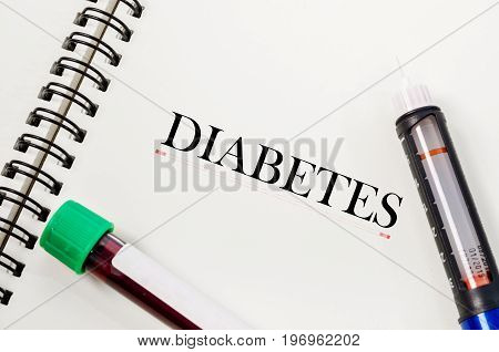 Book of diabetes disease with insulin syringe and sample blood test in blood tube.