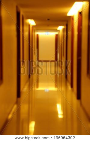 Blurred scene of hallway of apartment building in yellow tungsten light.