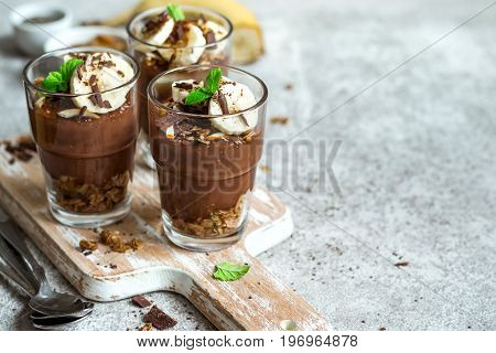 Chocolate pudding with chia and banana in glasses. Healthy dessert or breakfast.