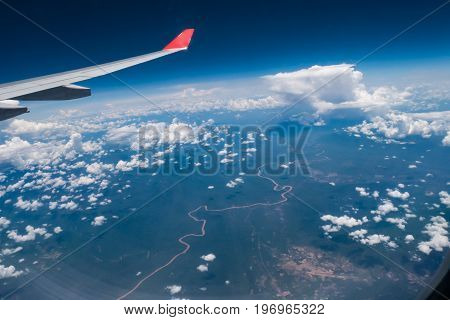 View from airplane window showing airplane wing with blue sky white clouds and small river underneath.