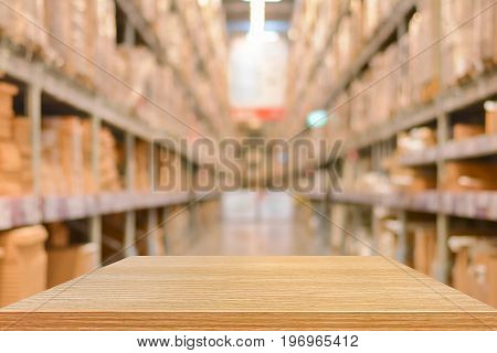 Empty wood table top (or shelf) on blurred warehouse background - can montage or display your products