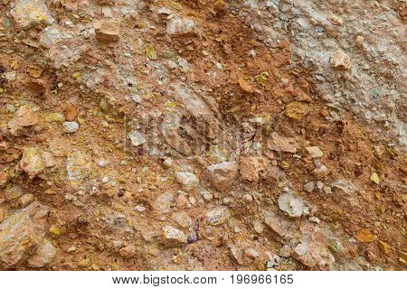 Red and white loam surface with parts of camstone. Textured background.