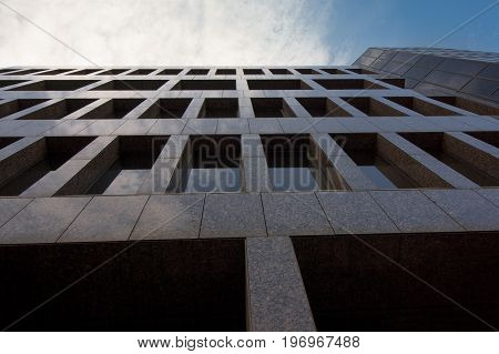 The dark facade of a tall office building in downtown