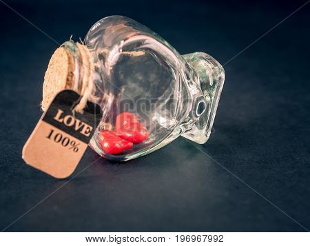Retro red heart in shape bottle on black background. LOVE and valentine's day concept.
