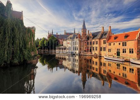 Historical centre of Bruges  in the evening sunlight. Bruges river view. Old Bruges buildings reflecting in water canal. Vibrant blue sky over Belgium landmarks.