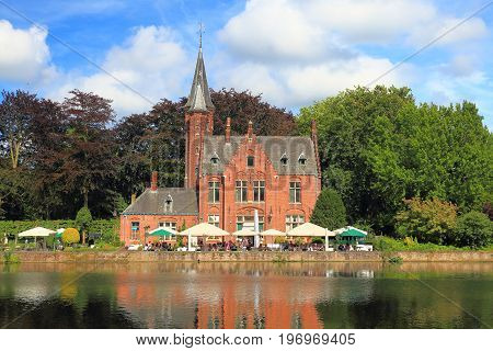 Landmarks of Bruges. Old red brick building with tower on water canal on a sunny summer day.