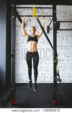 Young fitness woman preparing to do pull ups in pull up bar