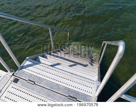 Modern jetty pier made of metal by the ocean beach