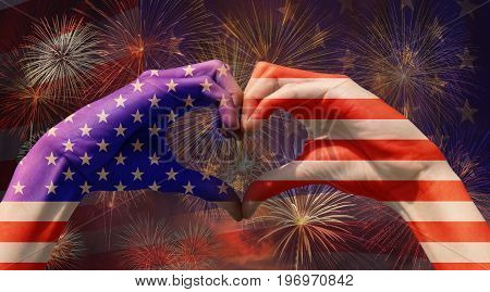 hands forming be heart for love with USA National flag over the Multicolor Fireworks Celebrate over the United state of America flag background Independence day concept