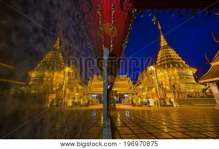 Amazing beautiful reflect of golden pagoda in twilight. At Wat Phra That Doi Suthep temple is tourist attraction of Chiang Mai, Thailand.