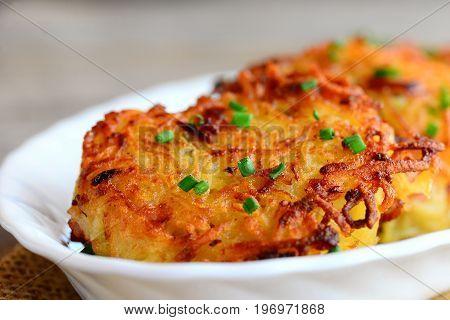 Golden potato burgers with ham on a white plate. Simple roasted potato ham burgers recipe. Closeup