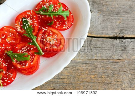 Tomatoes and arugula salad. Homemade fresh tomatoes, arugula and sesame salad on a white plate and vintage wooden background with copy space for text