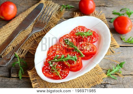 Tomato, arugula salad. Tasty and diet salad with tomatoes, arugula and sesame seeds on a white plate. Fork, knife, burlap textile on a vintage wooden table. Rustic style