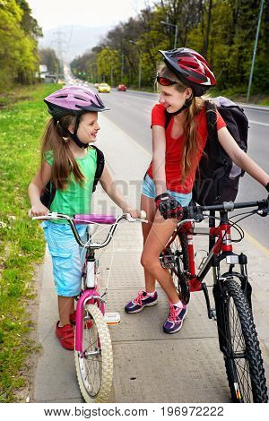 Bikes bicyclist girl wearing bicycle helmet and glass with rucksack ciclyng. Cycling on bike lane at city street. Kids are advised about route. Friendship between children of different ages.