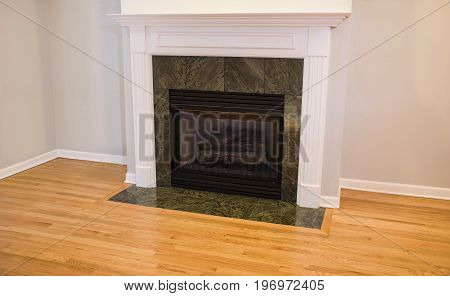 Fireplace with green granite around, new installed wood floor and white walls and crown moldings
