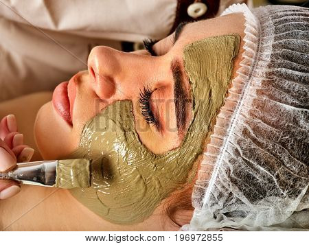 Mud facial mask of woman in spa salon. Massage with clay full face in therapy room. Healing clay to preserve youth.