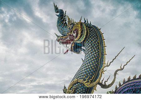 Chiang Rai Thailand - July 12 2017: Naga Head Statue Inside Wat Rong Sua Ten Or Blue Temple At Rain Clouds Background.