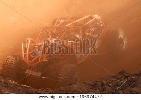Orange Roll Caged Car In Dugout With Red Dust Suspended In Air.