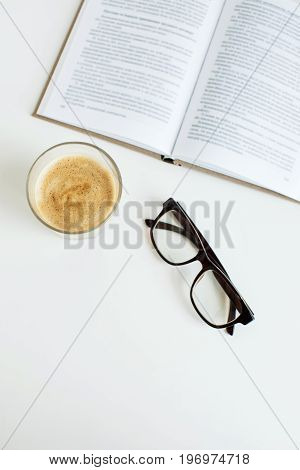 Top View Of Coffee In Glass, Eyeglasses And Book On Tabletop, Isolated On White