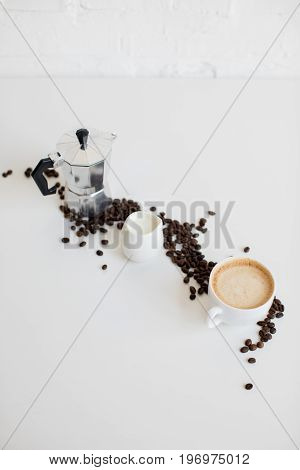 French Press, Cup Of Coffee And Milk Jar With Scattered Coffee Beans On White Tabletop
