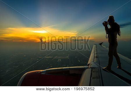 silhouette of photographer taking photo on airplane wing can see Fantastic twilight with sunset Challenge concept
