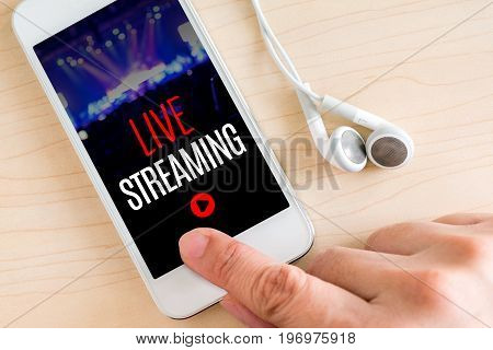 Hand Touch Smart Phone And Ear Phone With Live Streaming Word On Wood Table ,internet Marketing Conc