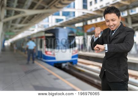 Young businessman looking at watch which cheerful action on abstract Blurred photo of sky train at station with security guard business rush hour concept
