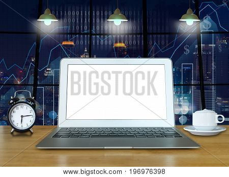 Workspace with computer laptop on the wood table with the windows which shown trading graph on the blurred photo of cityscape building background trading technology concept