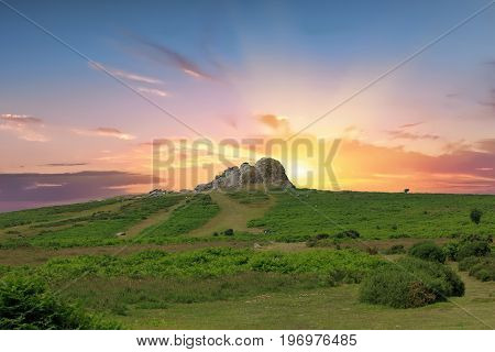 Haytor Rocks in Dartmoor at sunrise with a pink and yellow sky.