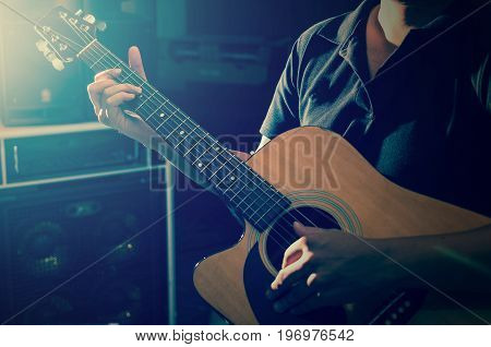 Closeup musician playing the guitar on band background with spot light musical concept