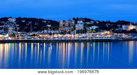 Torquay promenade at dusk with brightly coloured lights illuminating the bay with good reflections in the sea