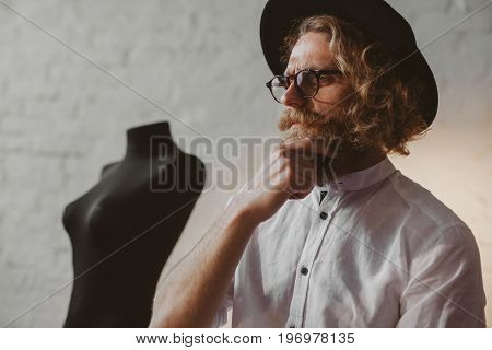 Young trendy man in hat and glasses posing thoughtfully in parlour.