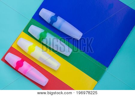 Bright Colored Markers Or Felt Pen Are Located On Sheets Of Colored Paper.