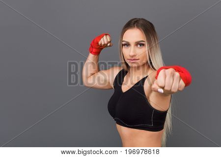 Adult sportswoman in red gloves holding hand outstretched and looking at camera on gray background.
