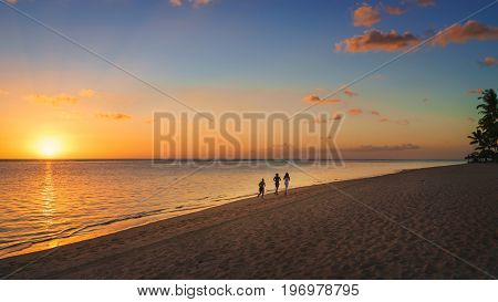 Thtree silhouette running on the beach at sunset in Mauritius.