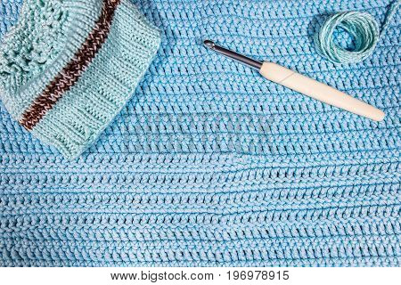 Little Beanie, Crochet Hook And Yarn On Blue Crocheted Cloth