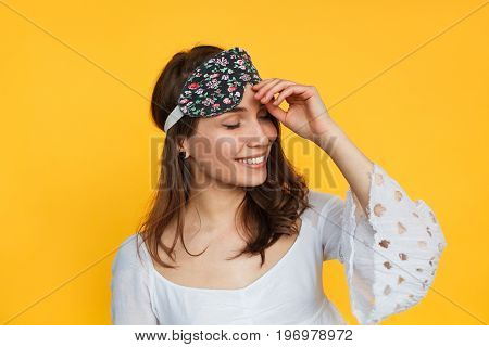 Young woman looking happy and posing in sleeping mask on yellow background.