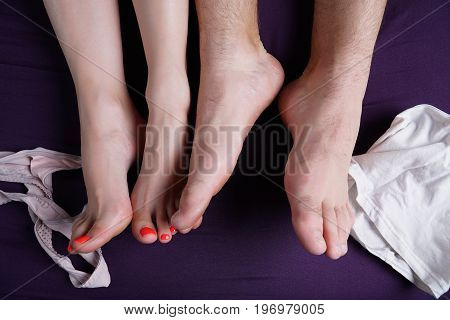 Female and male feet lie on a violet sheet. Nearby underwear is strewn. Lovers after sex.