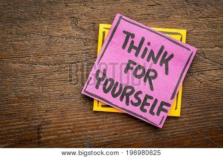 Think for yourself reminder or advice - handwriting on a sticky note against rustic wood