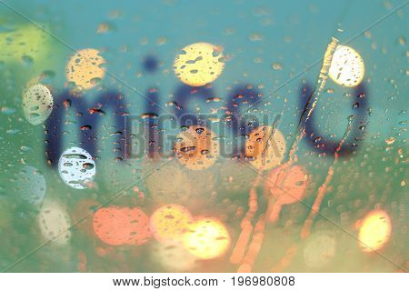Rain drops and miss you text on window with light bokeh rainy season abstract background.