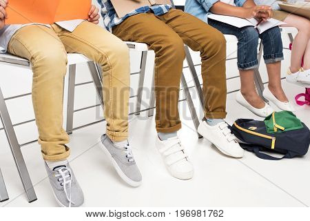 Cropped Shot Of Children Reading Books While Sitting On Chairs Isolated On White