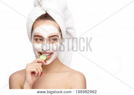 Lovely young woman with cleansing mask on face biting slice of cucumber on white background.
